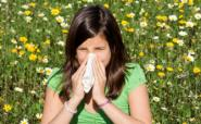 child with hayfever blowing her nose in a meadow