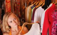 woman choosing from rack of clothes
